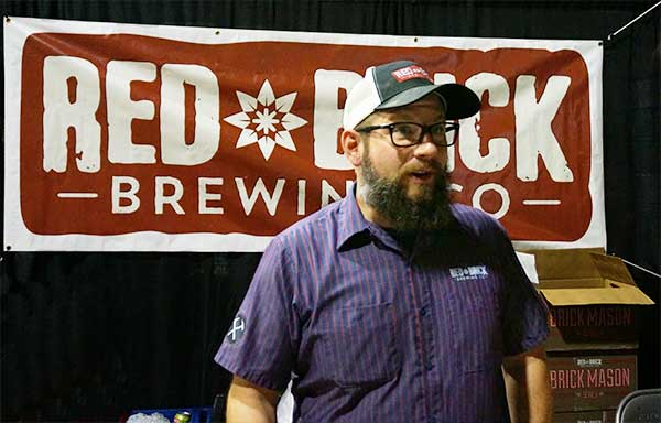 Red Brick Brewing Rep talks with Porch Drinking staffer in front of brewery banner