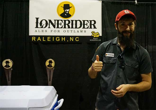 Lonerider rep poses with thumbs up next to kegerators