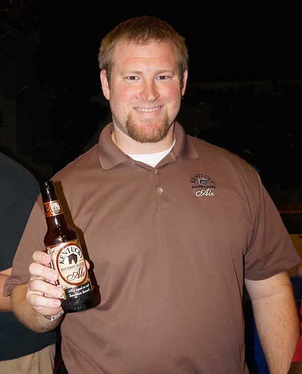 Alltech Kentucky Bourbon Ale Rep poses with bottle of Bourbon Barrel Ale