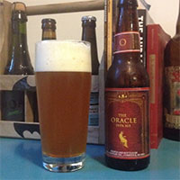 Empty bottle of Bell's The Oracle double IPA next to a glass filled with the same.