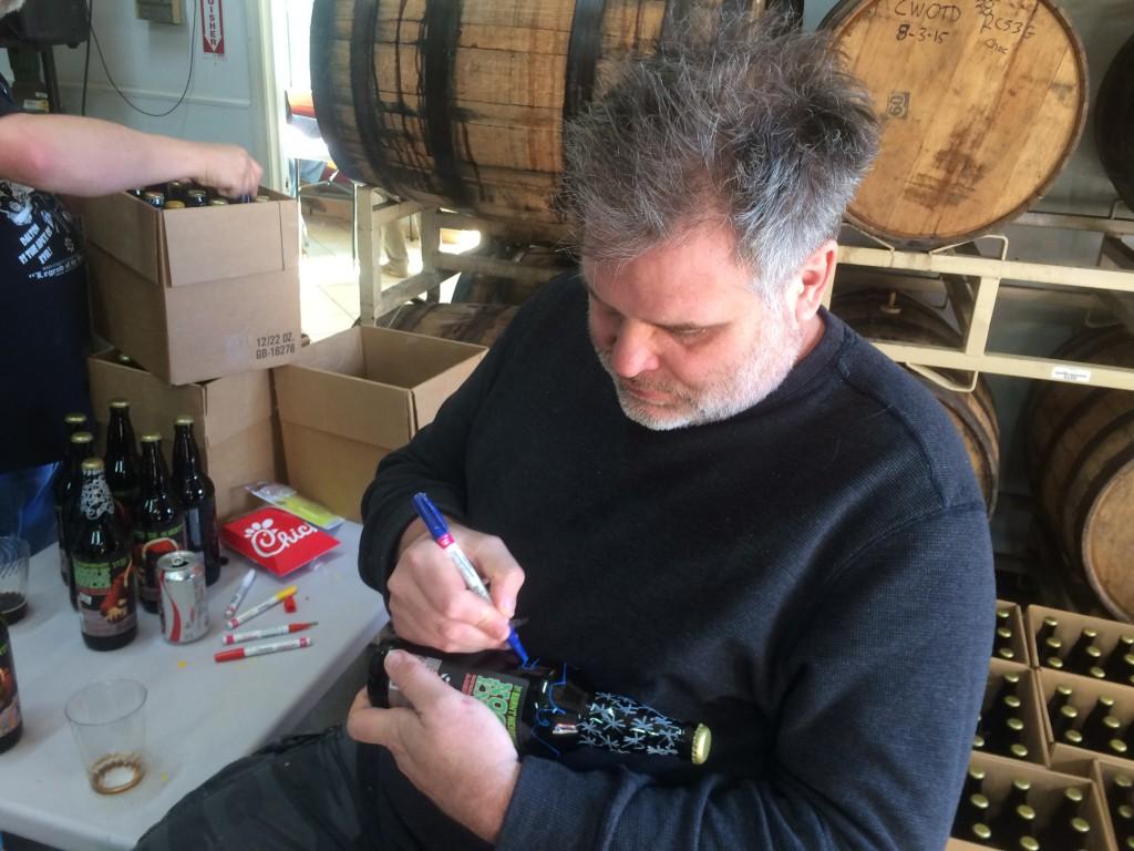 Owner Scott Hedeen signing bottles