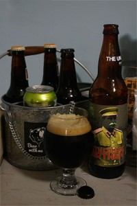 Glass of Dirty Commie Heathen along side the bottle with bottles and cans of other beers in the background