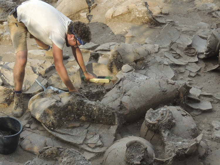 Archaeologist Benjamin Gates unearthing ancient barrels used to age Egyptian beer.