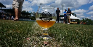 Augusta Beer Fest glass sitting on grass with a blue cloudy sky overhead