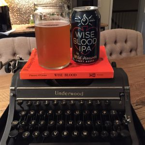 Wild Heaven Wise Blood IPA can and glass atop orange O'Connor novel on top of black typewriter