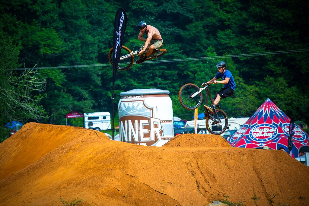BMX bikes doing stunts on dirt ramps at Oskar Blues Burning Can NC