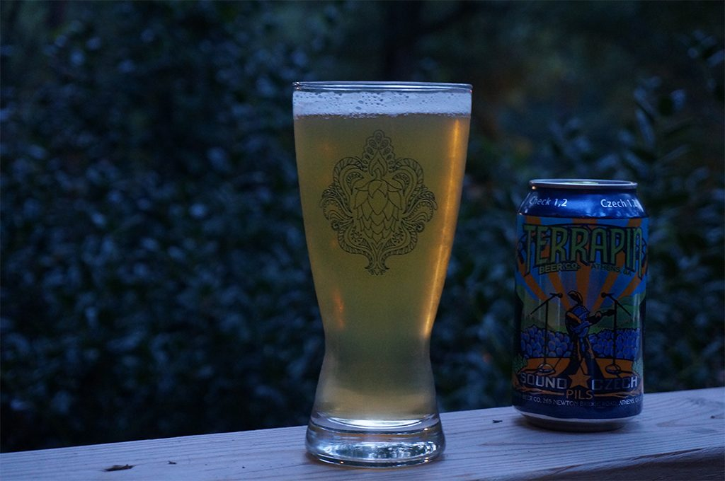 A glass of Sound Czech Pilsner neck to a can of the same on a porch railing.