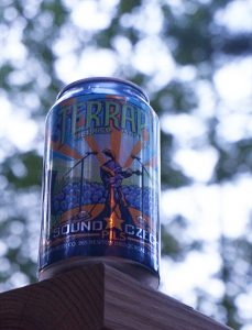 A can of Terrapin Sound Czech Pilsner prominently positioned on the edge of a porch railing.