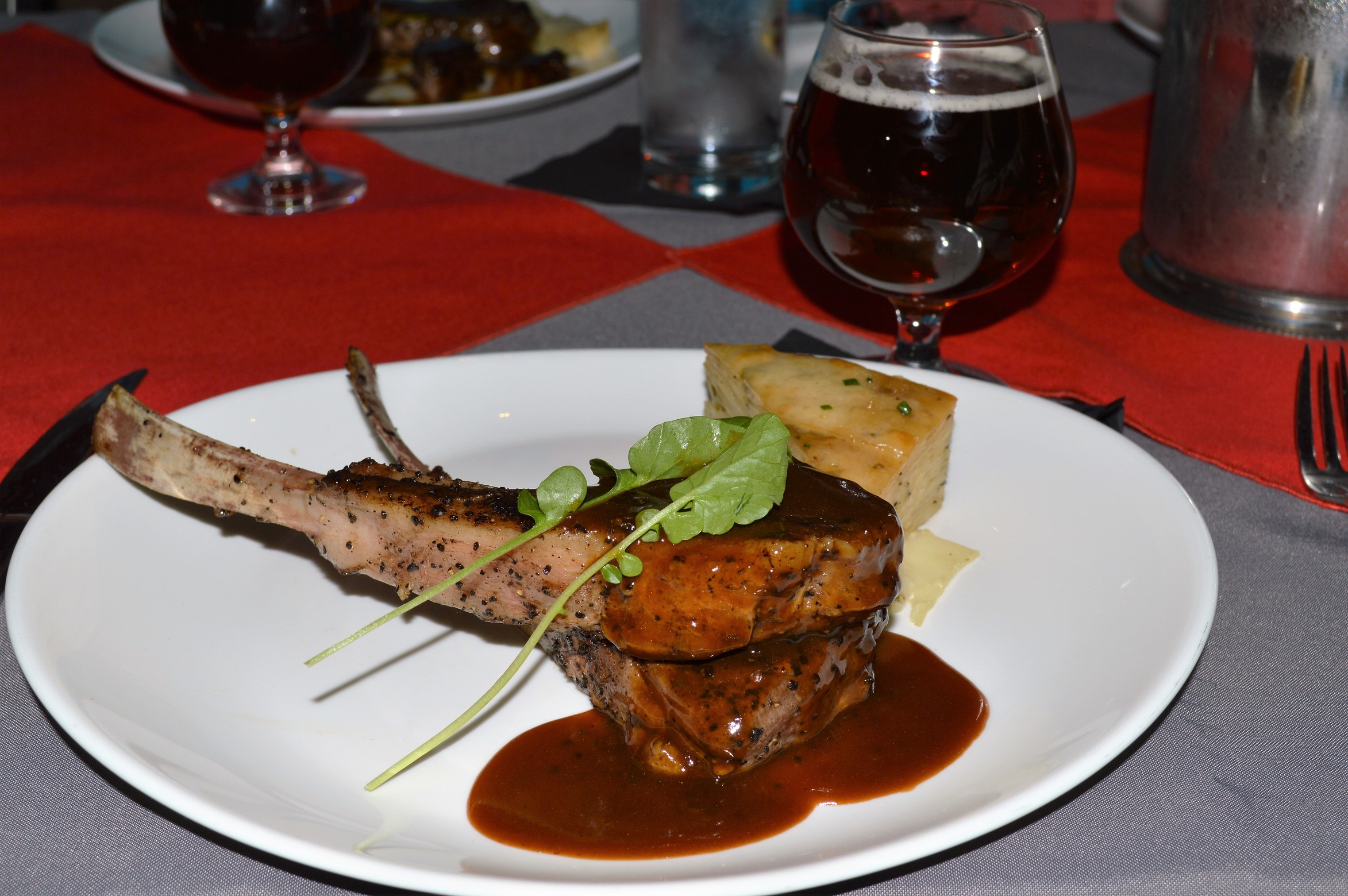 Expresso-encrusted Colorado lamb lollipops, white cheddar potato gratin, and water cress, with a 90 Schilling demi-glace.