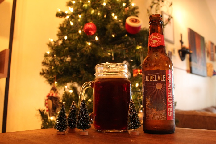 A full glass of Jubilale beer in front of a Christmas tree