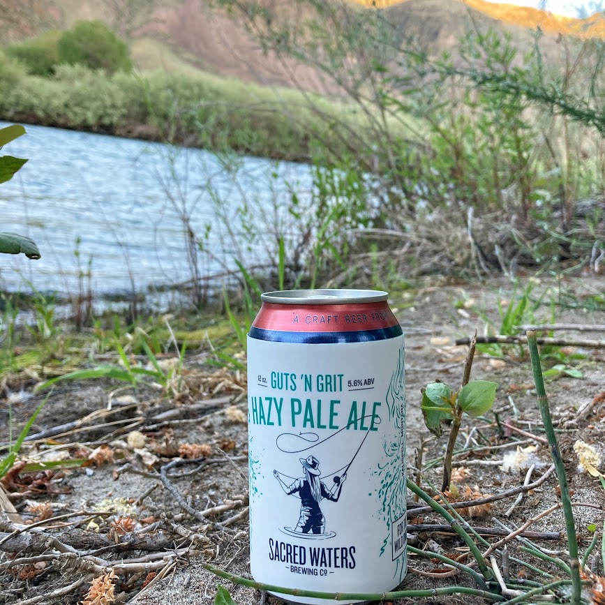 Guts N Grits Pale Ale can by a river
