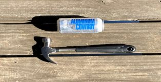 A can of Aluminum Cowboy beer lying next to a hammer